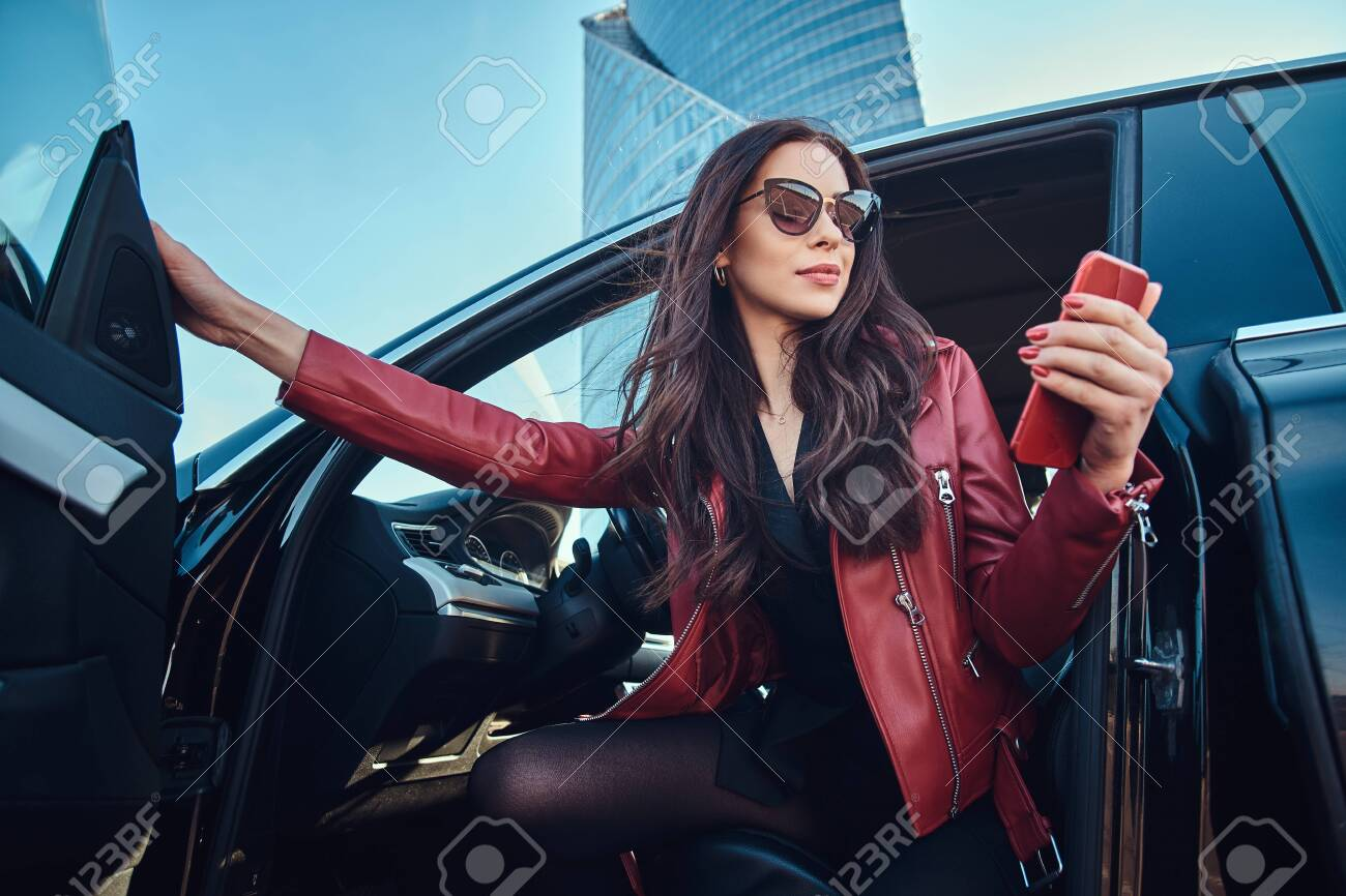 Beautiful smart women is posing in her new car while chatting on mobile phone. She is wearing red leather jacket and sunglasses. - 122080734
