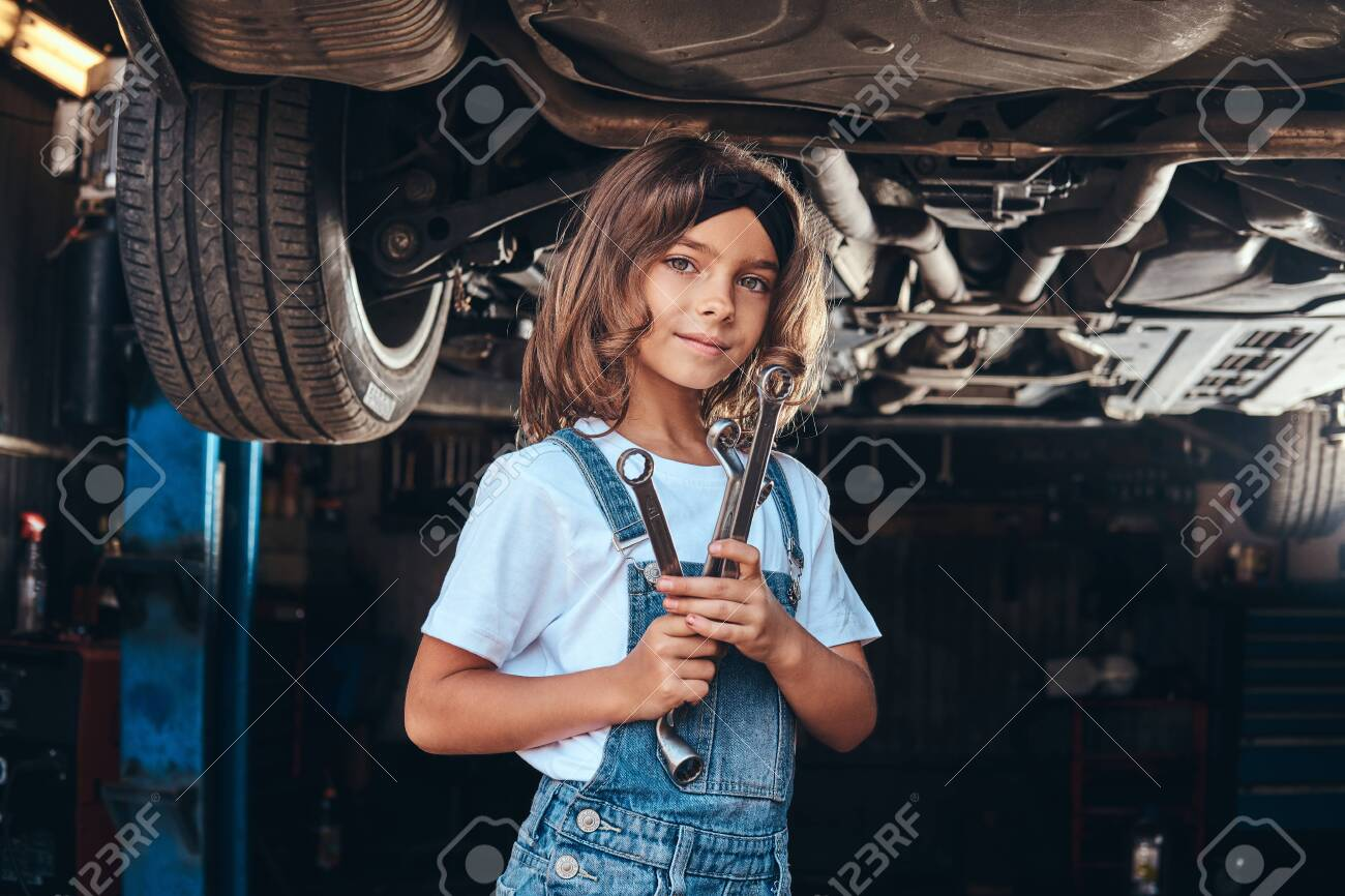 Happy smiling girl is standing under the car at auto workshop with wrench in hands. - 130260461