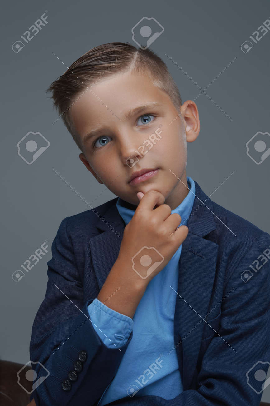 Pensive preteen boy dressed in suit against gray background - 172766956