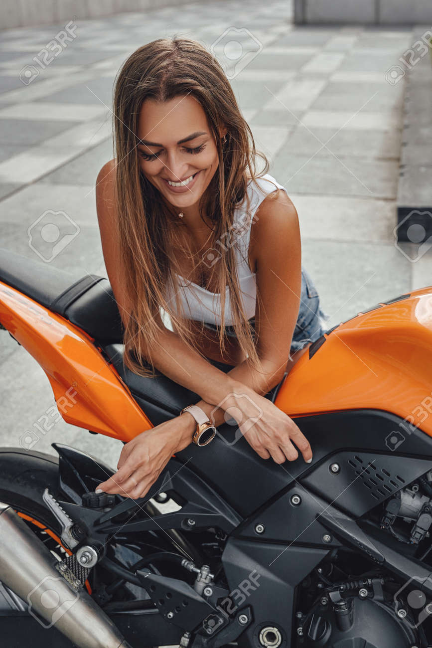 Joyful woman biker posing with orange motorcycle outdoors - 172796662
