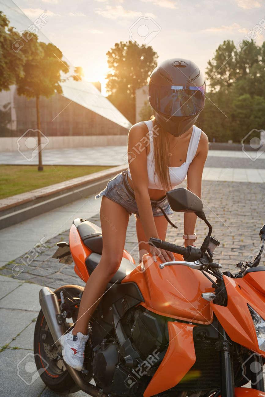 Female motorcyclist with helmet posing on motorbike outside - 172796629