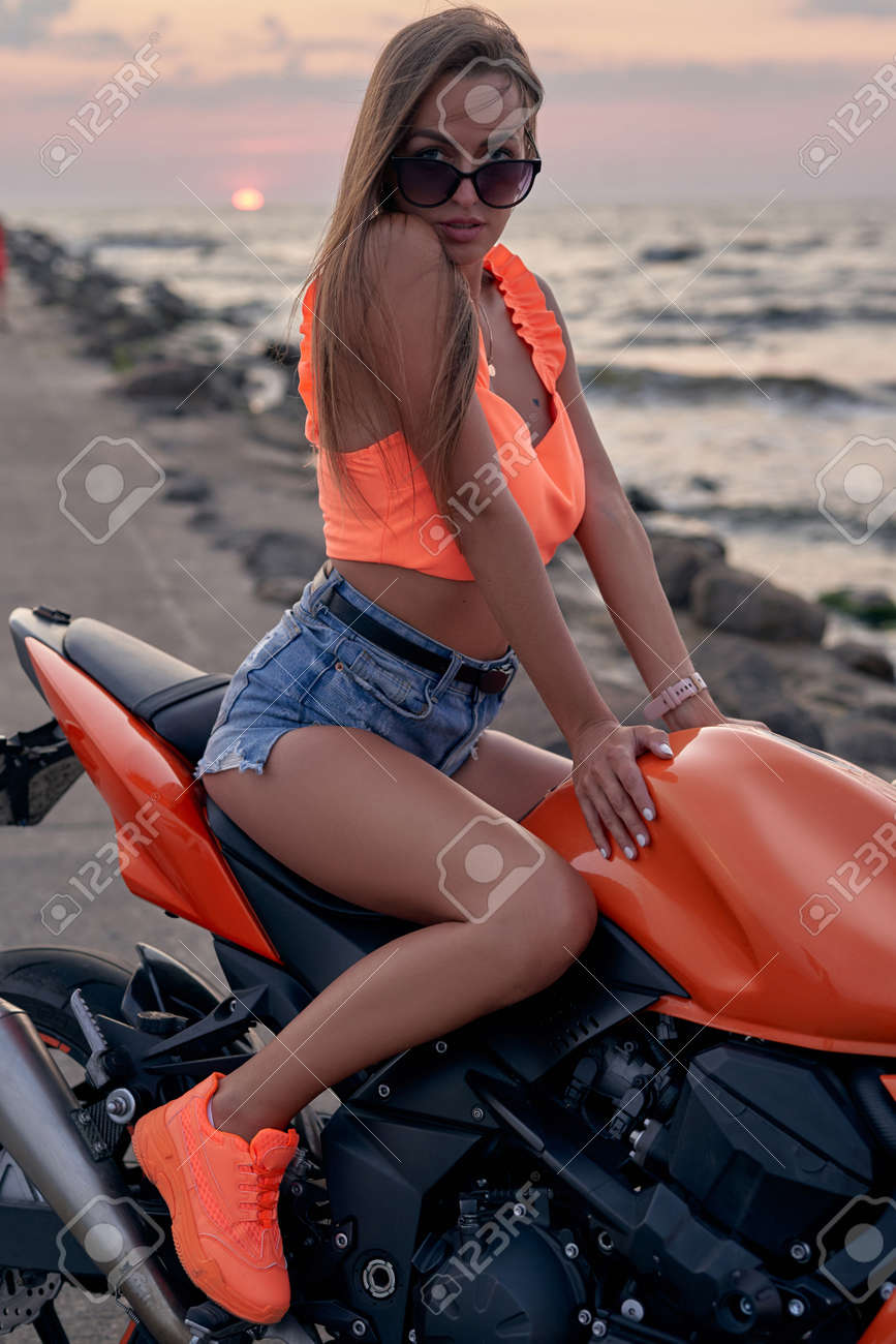 Tanned woman posing on orange bike on coast at sunset - 172796285