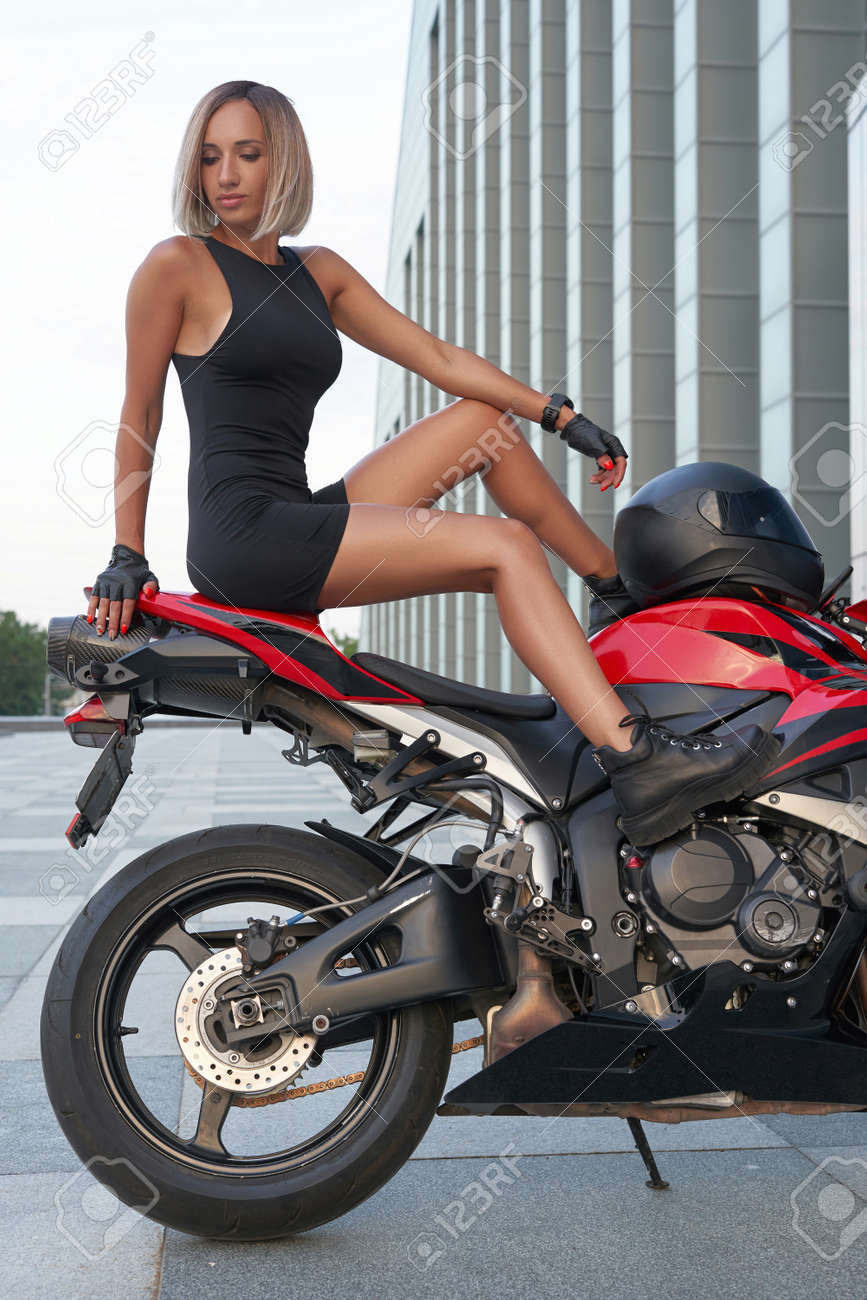 Blond haired sportswoman posing on red bike outside - 172807114