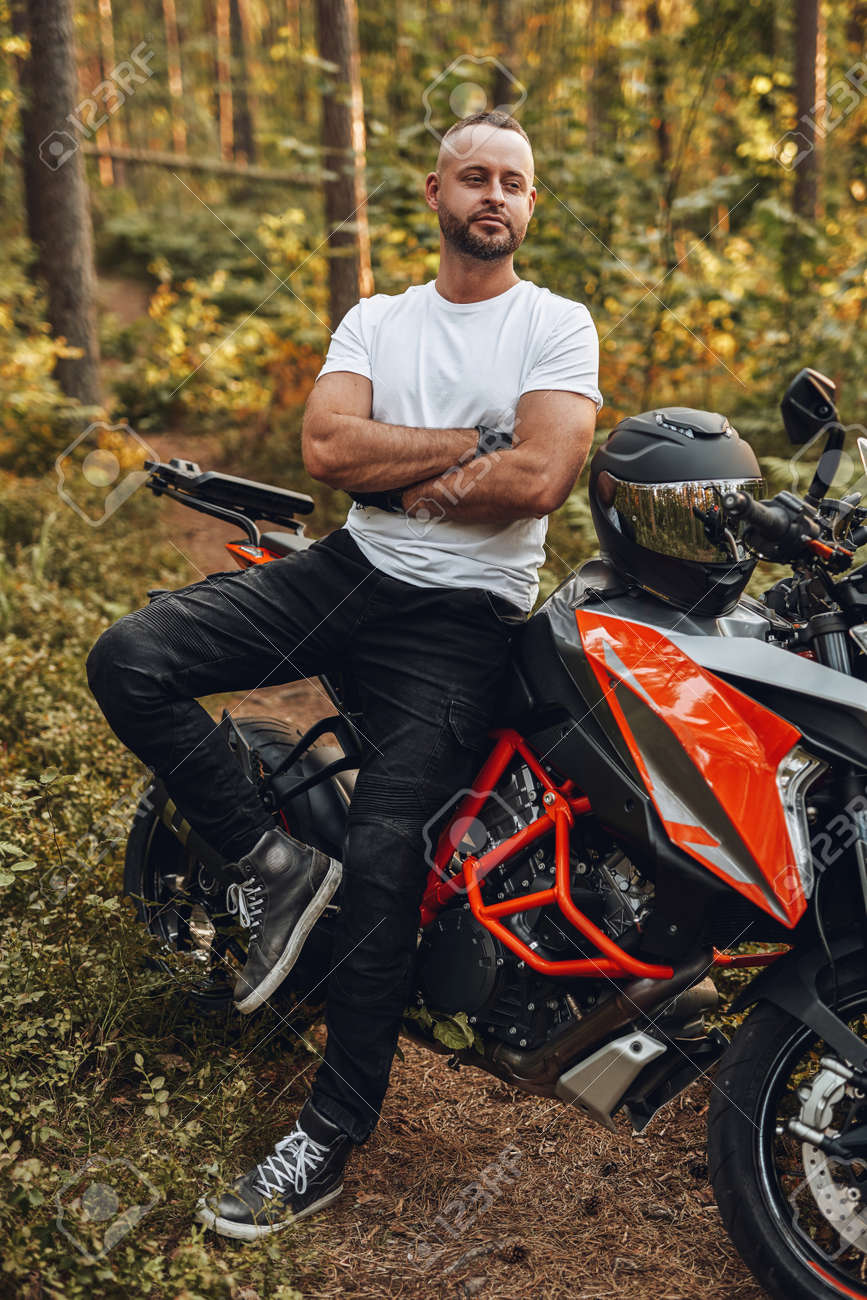 Bearded buy dressed in casual clothing with bike in forest - 172857264