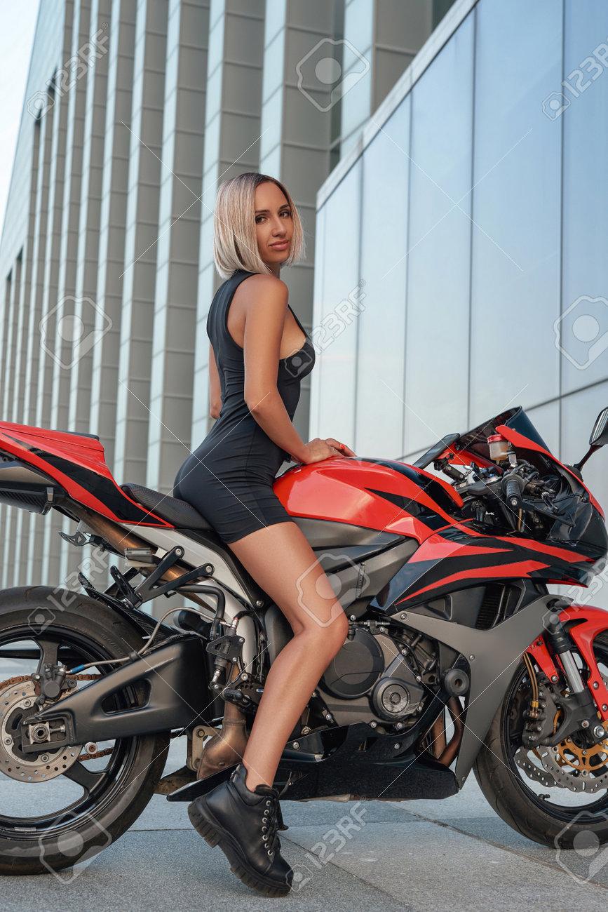 Female athlete biker with slim body riding red bike - 172904451