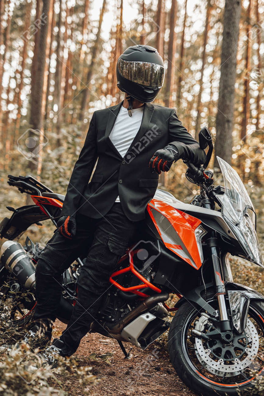 Man weared in black suit with dark motorcycle in forest - 172904835