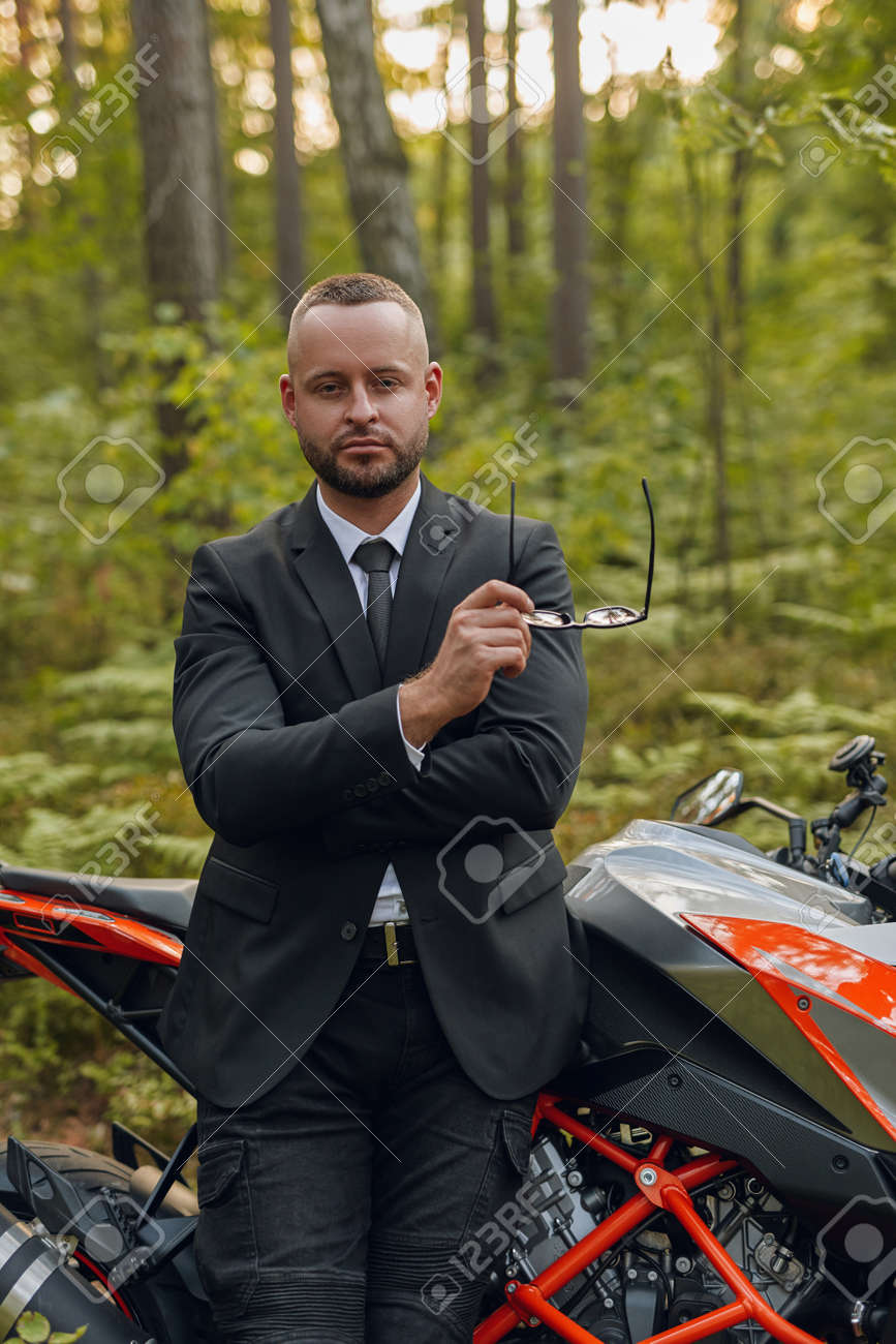Cool man and black red colored motorbike in forest - 172904675