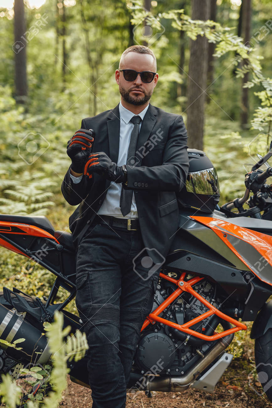 Businessman wearing protective gloves posing in summer forest - 172904767