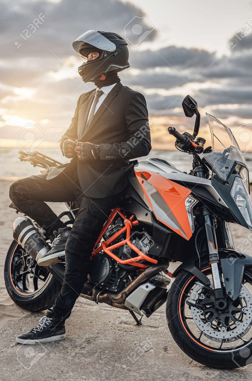 Cool businessman with motorcycle helmet posing against seascape - 172904882