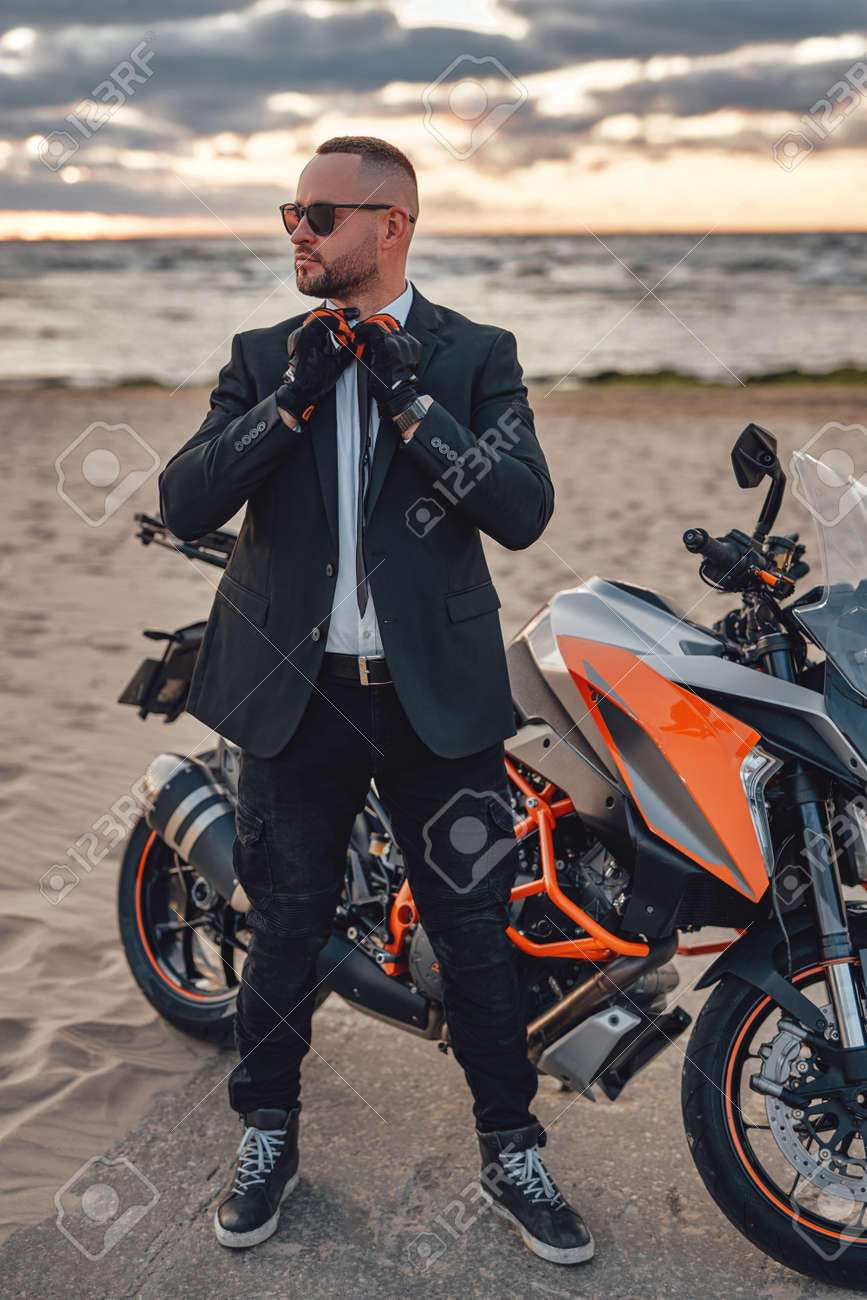 Cool guy with sunglasses and dark motorcycle on beach - 172904321