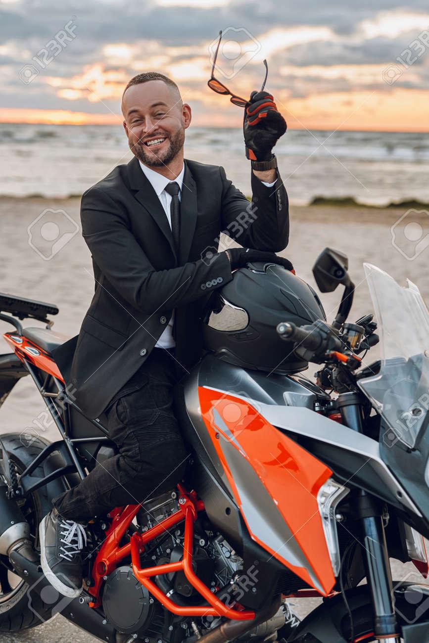 Joyful motorcyclist in suit riding sports bike on beach - 172904731