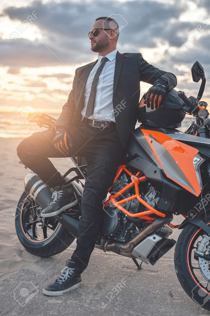 Male biker relaxing on beach with his sports motorbike - 172904378