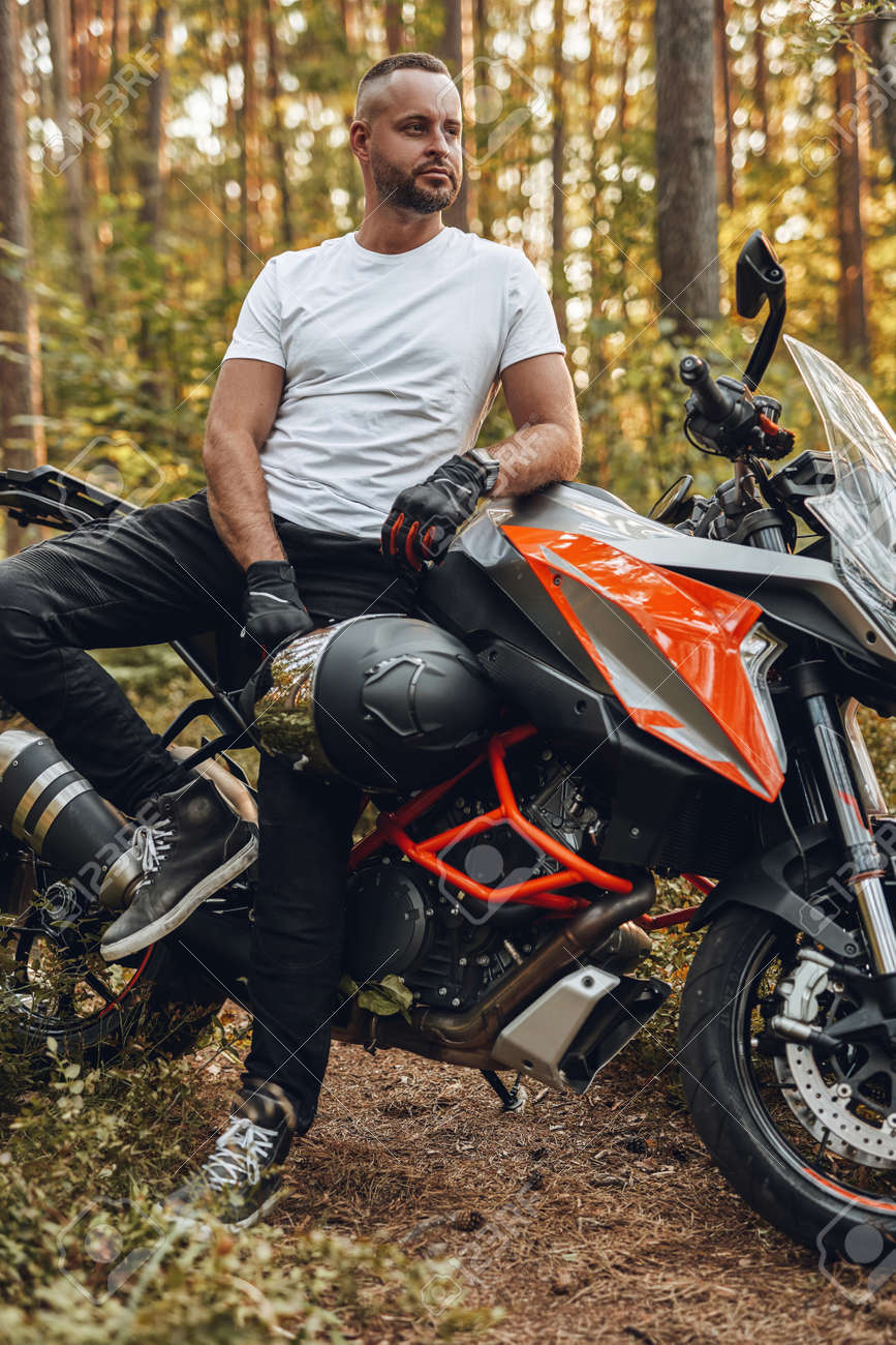 Bearded buy dressed in casual clothing with bike in forest - 172977475