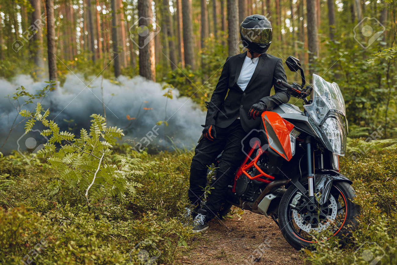 Cool biker in suit posing with bike against forest with smoke - 172977196