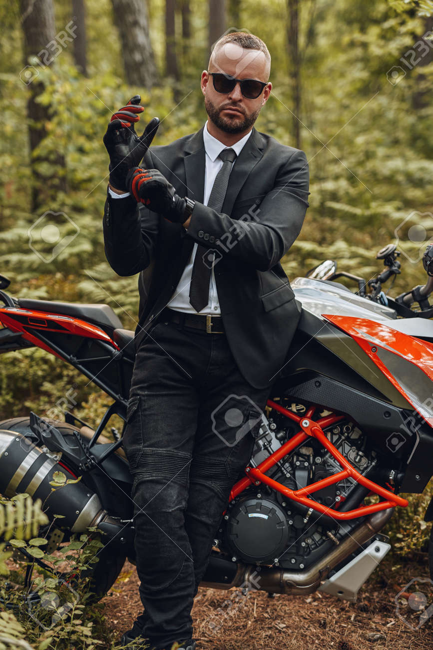 Businessman wearing protective gloves posing in summer forest - 172977510