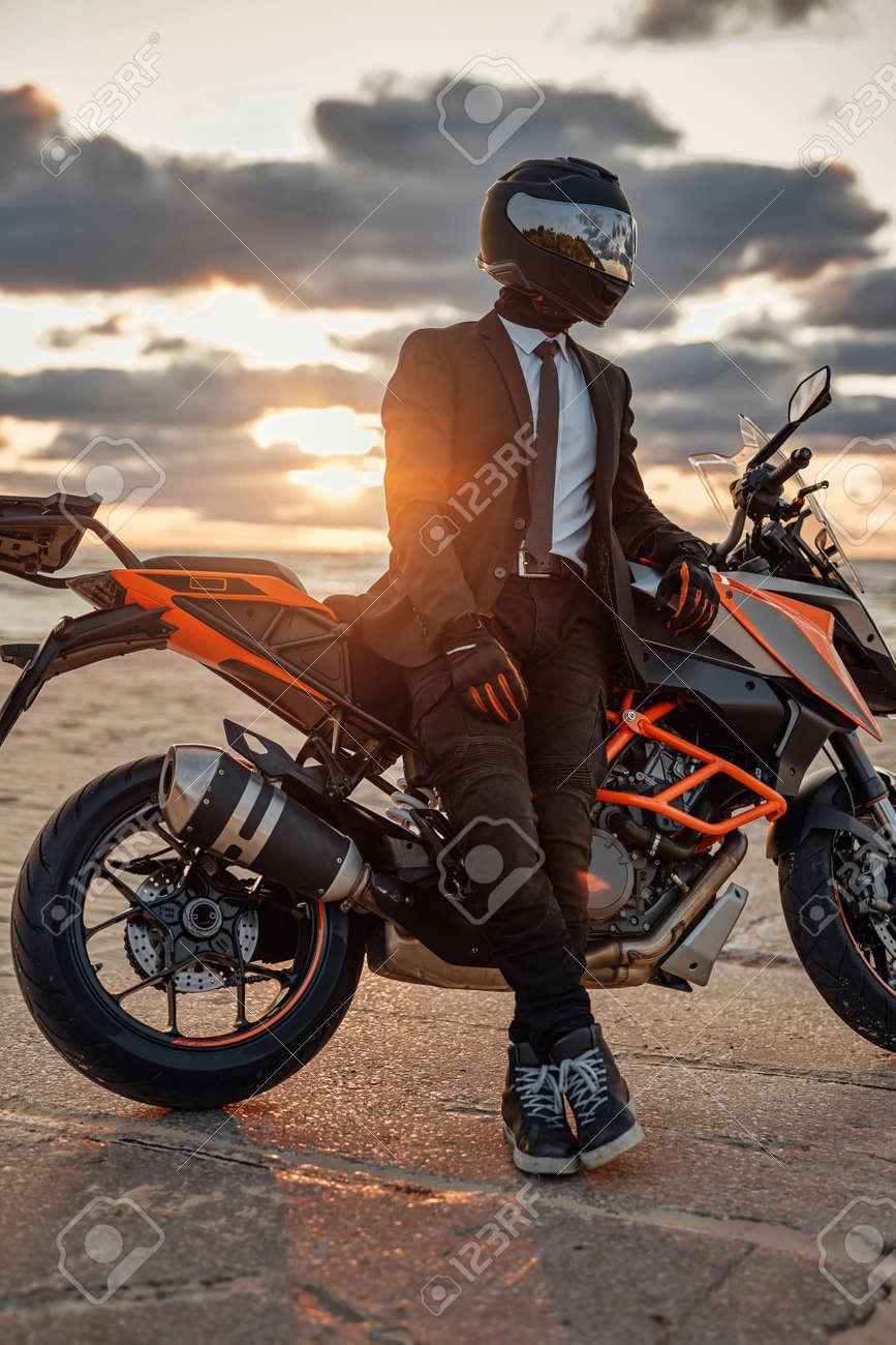 Man dressed in suit and helmet posing on beach with bike - 172976842