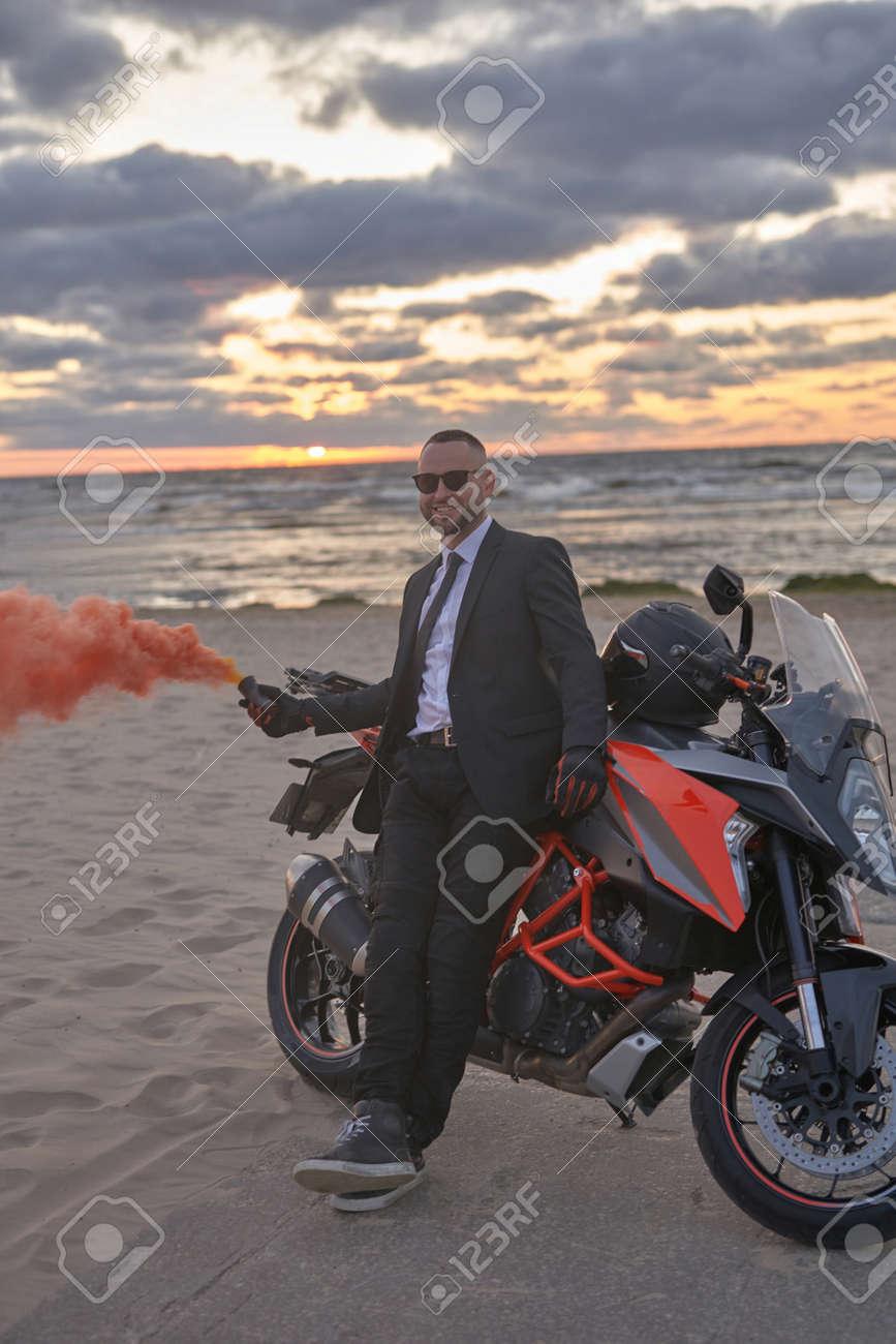 Stylish man with smoke bomb and motorbike on beach - 172976966