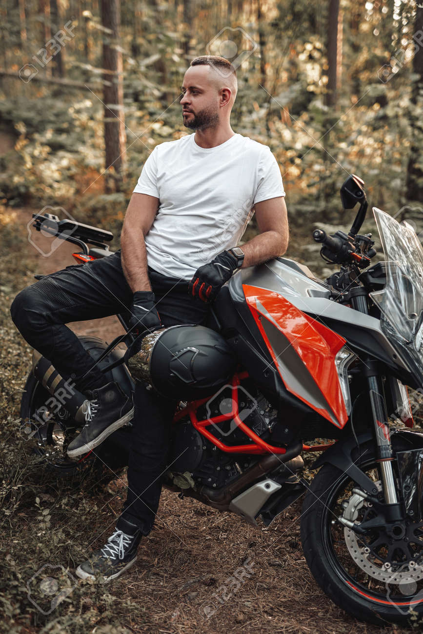 Bearded buy dressed in casual clothing with bike in forest - 173047740