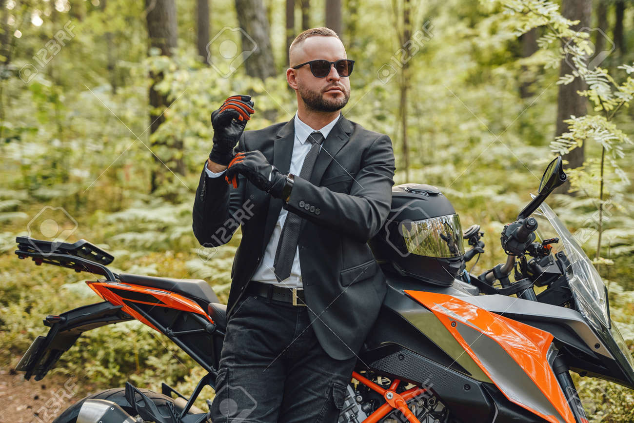 Businessman wearing protective gloves posing in summer forest - 173047930