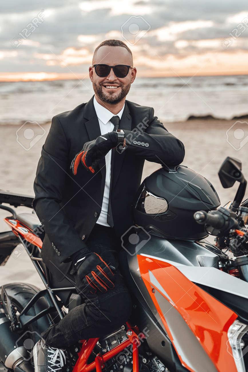 Joyful motorcyclist in suit riding sports bike on beach - 173047977