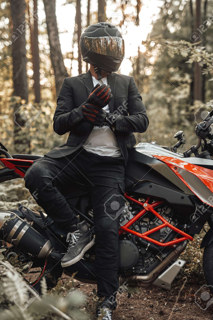Businessman biker with gloves and helmet posing in forest - 173047669