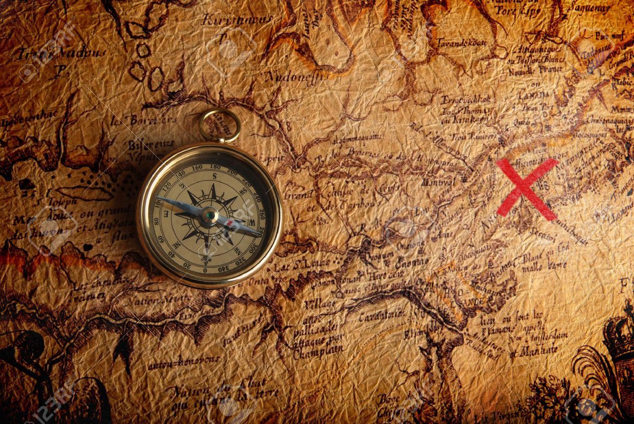 Old brass compass lying on a very old map showing the way to treasure - 6850429