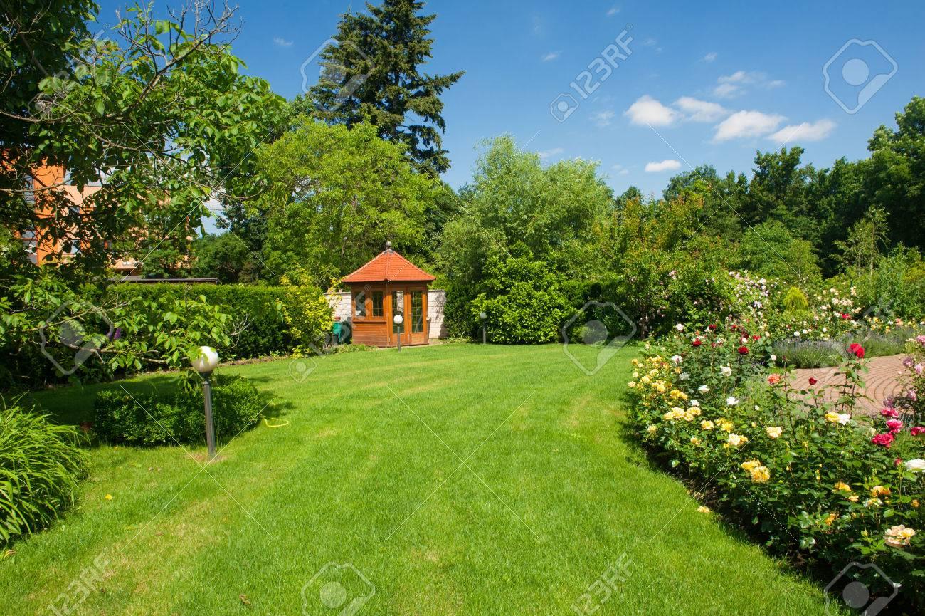 Schöner Garten Mit Blühenden Rosen, Backstein Pfad Und Ein Kleiner Pavillon  Standard Bild