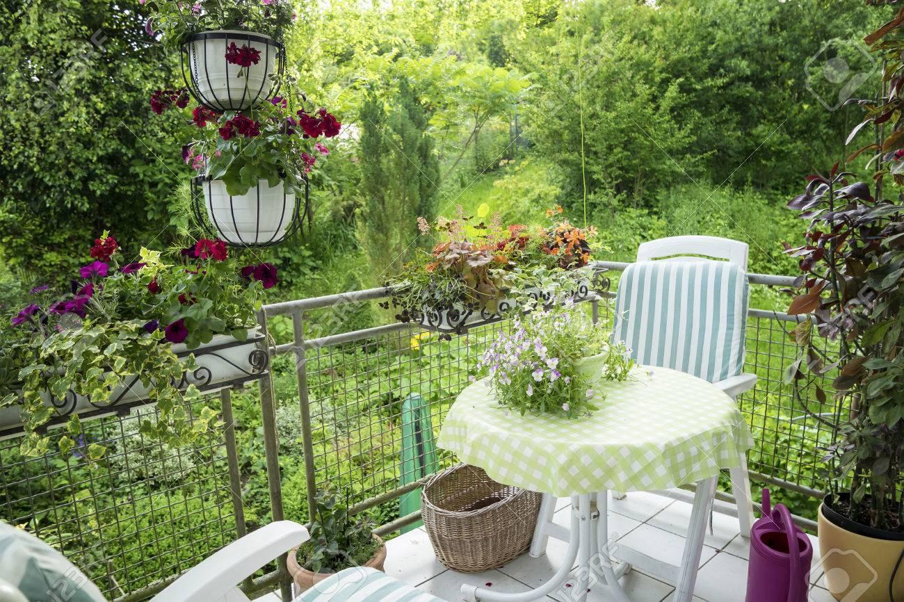 Terraza De Verano O Balcón Con Una Pequeña Mesa Silla Y Flores