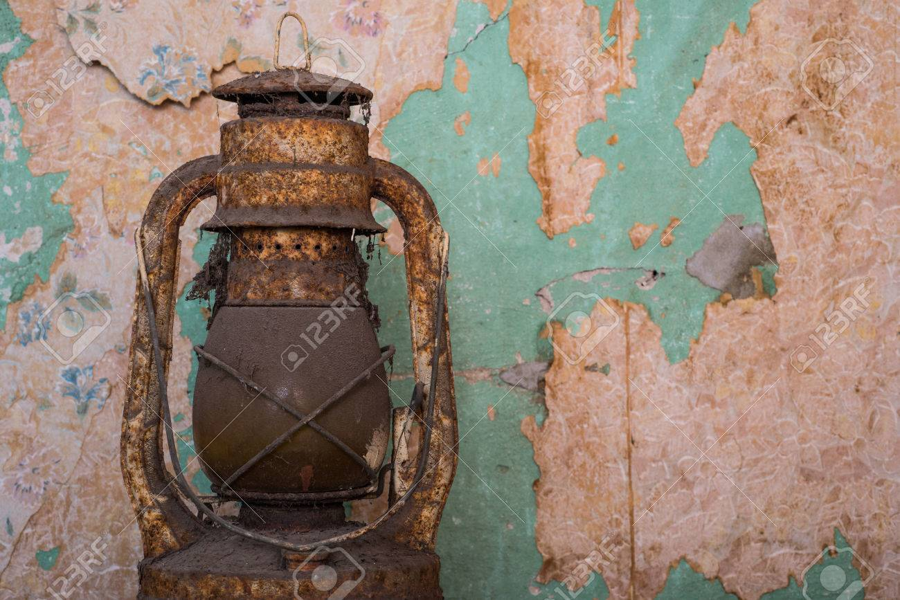 Old rusty antique oil lamp, abandoned building peeling wallpaper background. Stock Photo - 56751971
