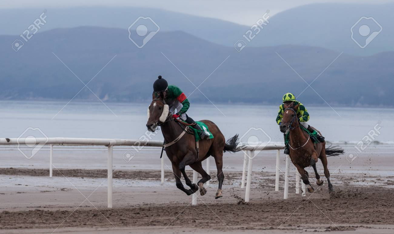 Galloping Race Horse And Jockey On The Beach Stock Photo