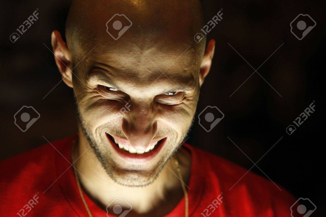 terrifying man with a grin as a smile looking at the camera with his chin down and the light under his face Stock Photo - 3309840