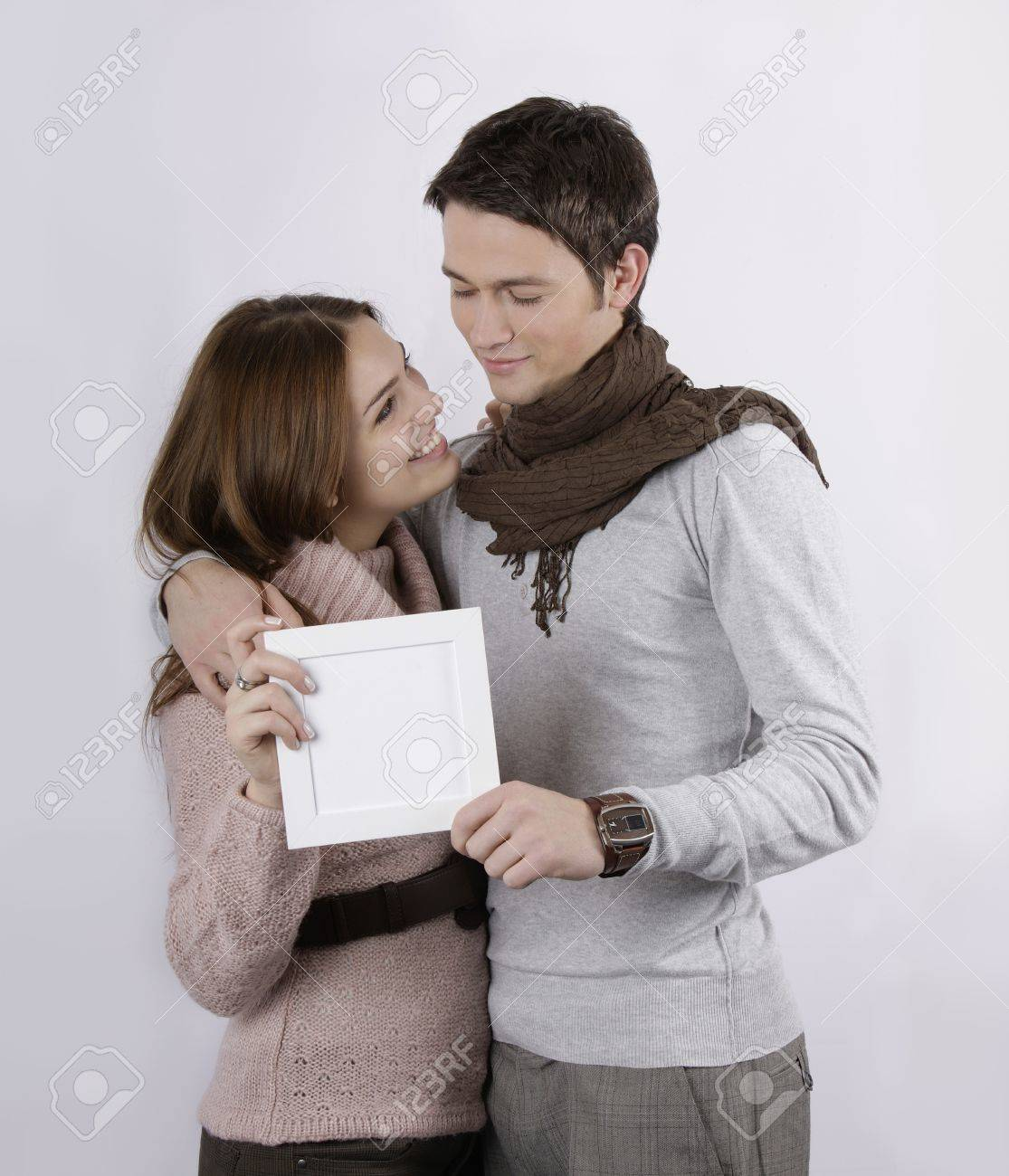 attractive couple holding frame Stock Photo - 4171052