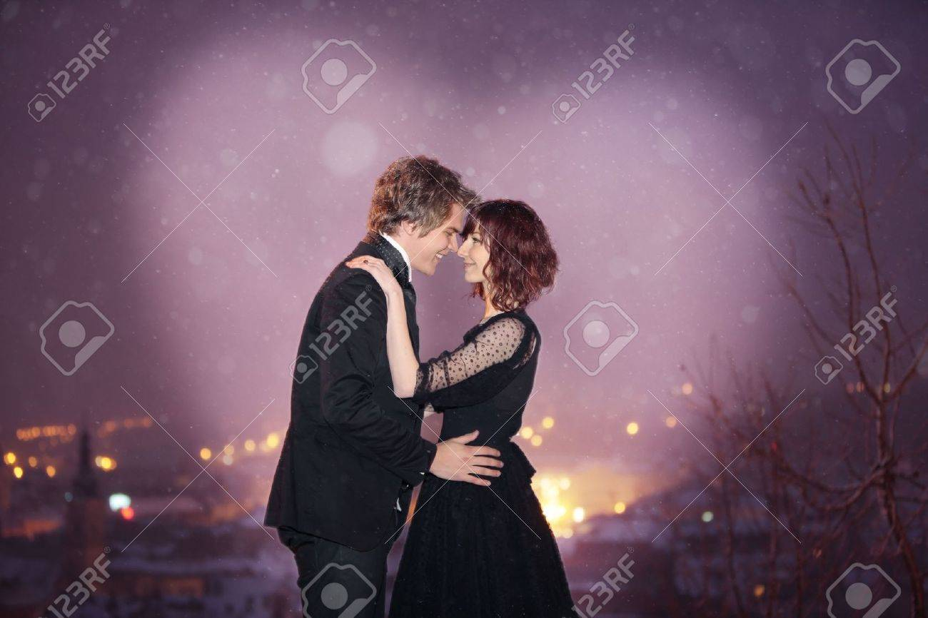 Profile of Romantic Couple smiling looking into each others eyes against the city at night on valentine's day Stock Photo - 8262025
