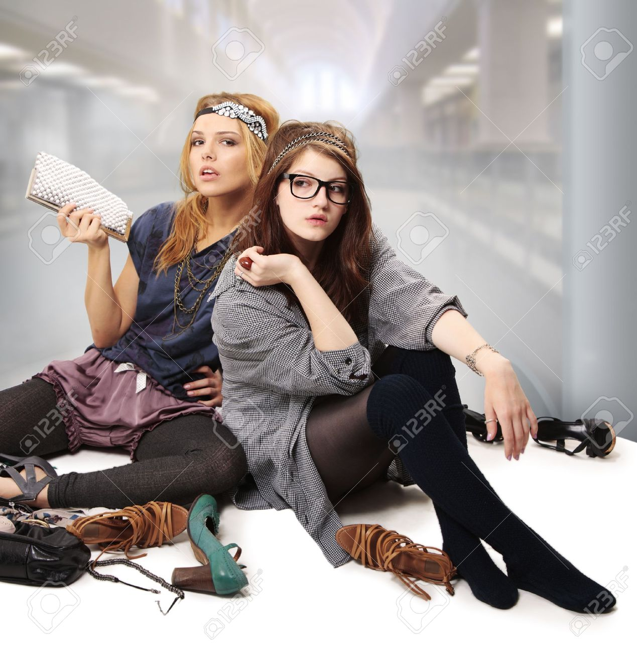 Cool teenage girls fashionista with headpiece standing on the floor surrounded by accessories, shoes and blings Stock Photo - 8852967