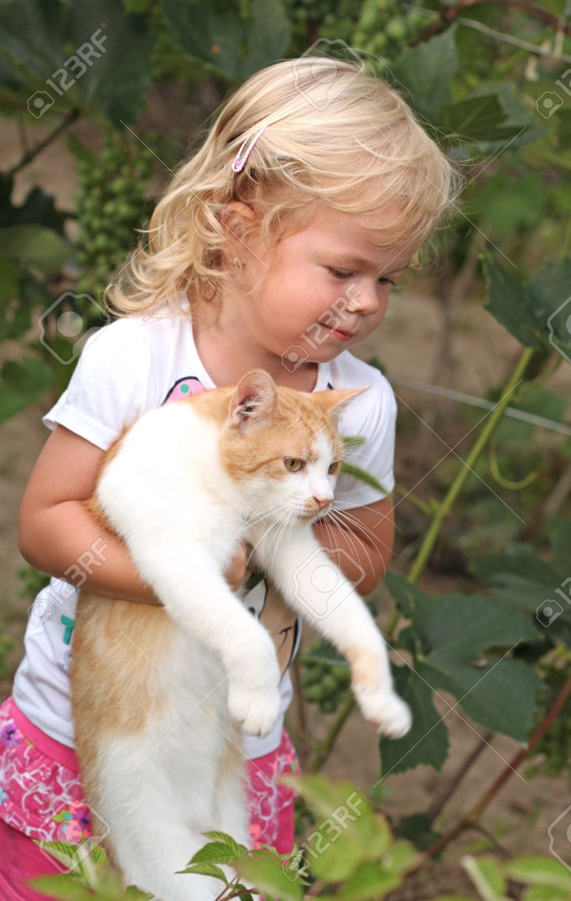 Cute little girl holding a red cat - 34846922