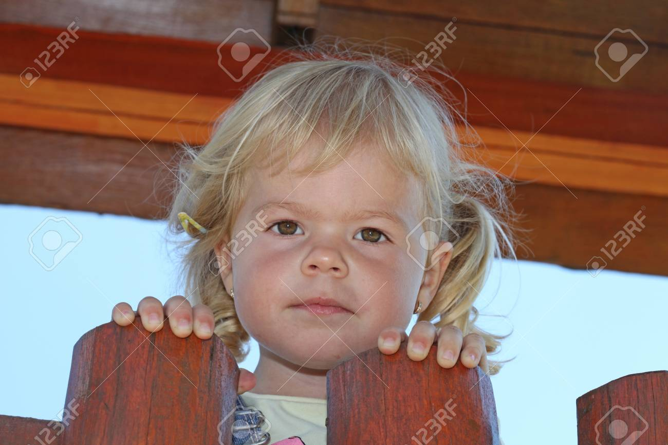 Portrait of cute blond girl holding on to wooden fence. - 34846924