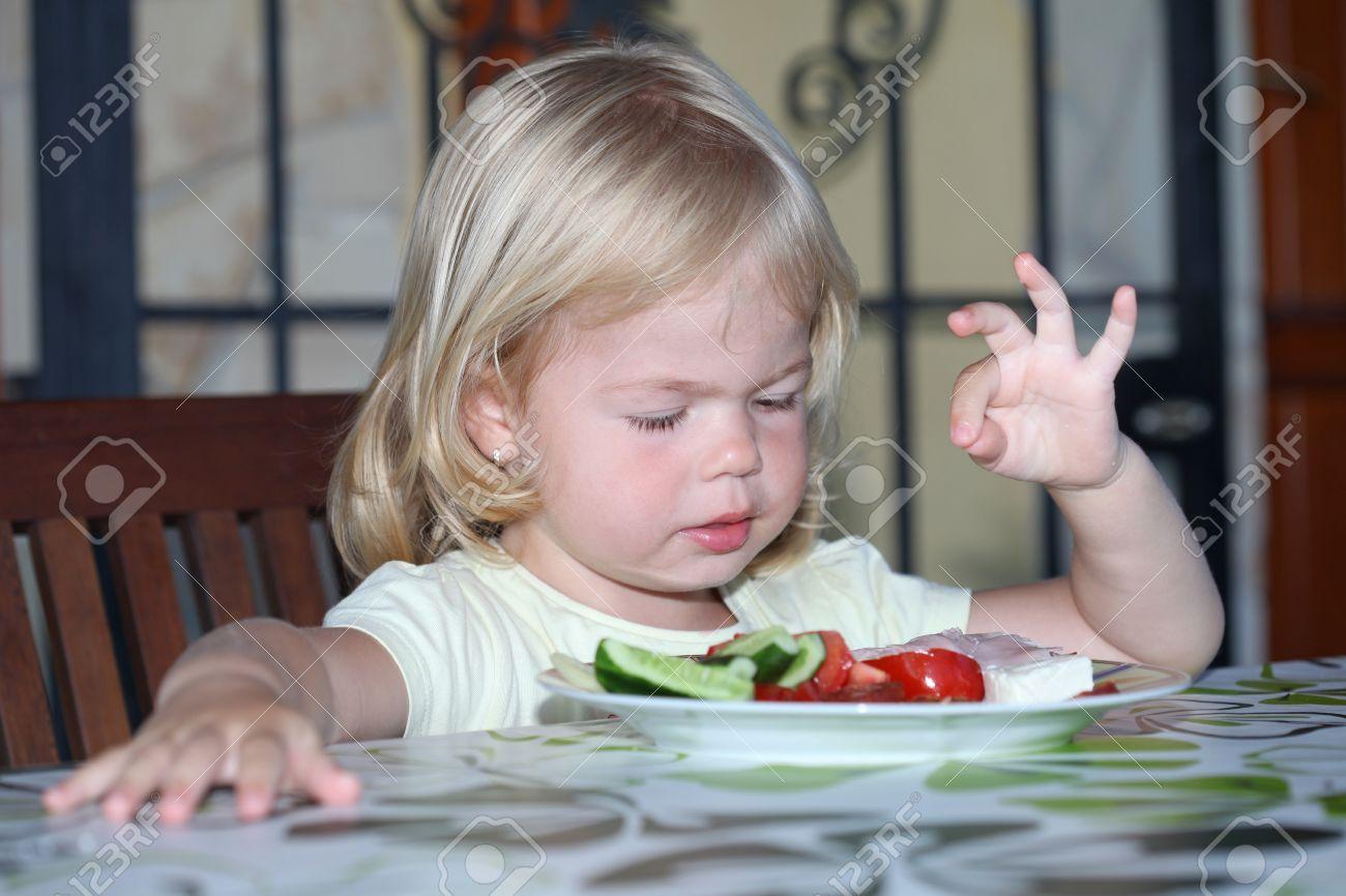 Portrait of sweet little girl having lunch - 34846925