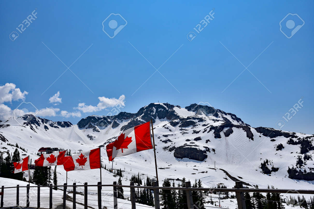WHISTLER, BC, CANADA, MAY 30, 2019: The Canadian flags on the top of Blackcomb mountain in Whistler Village. Whistler is a canadian resort town visited by over 2 million people annually. - 160784260