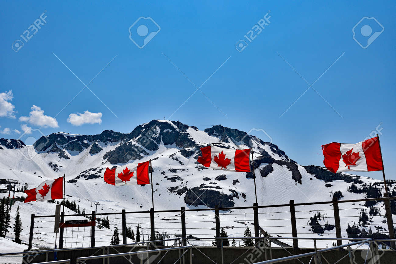 WHISTLER, BC, CANADA, MAY 30, 2019: The Canadian flags on the top of Blackcomb mountain in Whistler Village. Whistler is a canadian resort town visited by over 2 million people annually. - 160784251