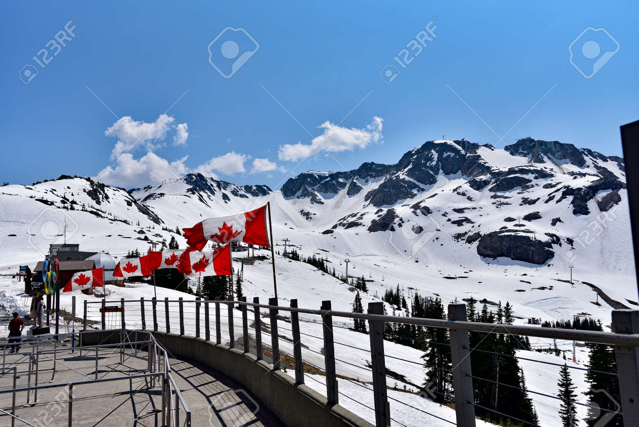 WHISTLER, BC, CANADA, MAY 30, 2019: The Canadian flags on the top of Blackcomb mountain in Whistler Village. Whistler is a canadian resort town visited by over 2 million people annually. - 160784266