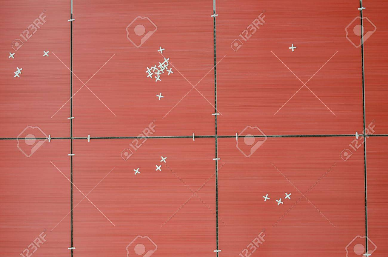 Top View Of Unfinished Red Ceramic Tiles With Tile Spacers Stock