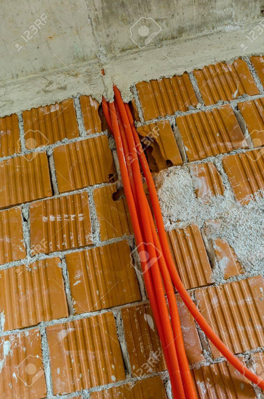 Orange Kunststoff-Rohre Für Elektrische Kabel Hängen Von Einer Mauer ...