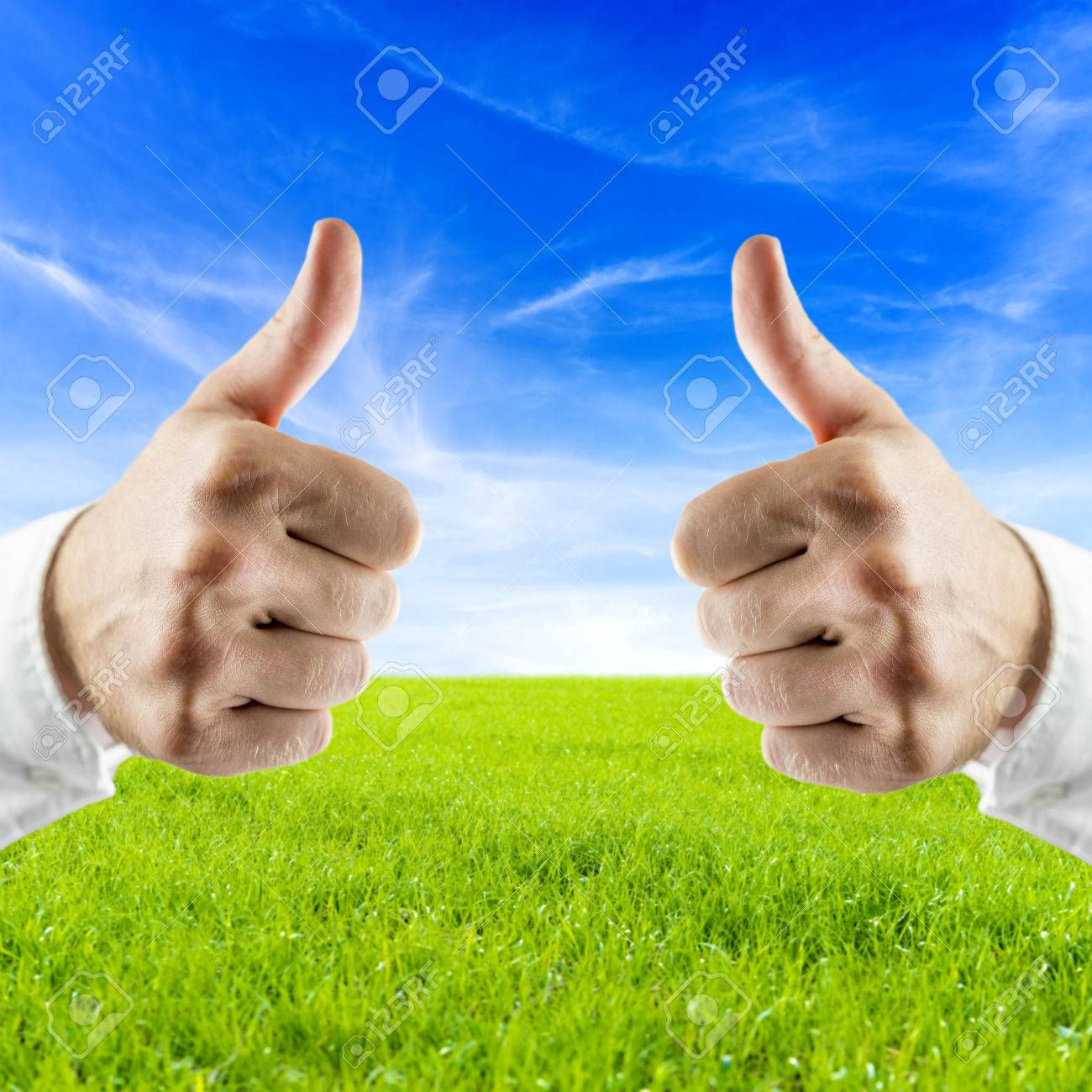 Closeup of male hand showing thumbs up sign with beautiful nature in background. Concept of saving the planet. Stock Photo - 24360866