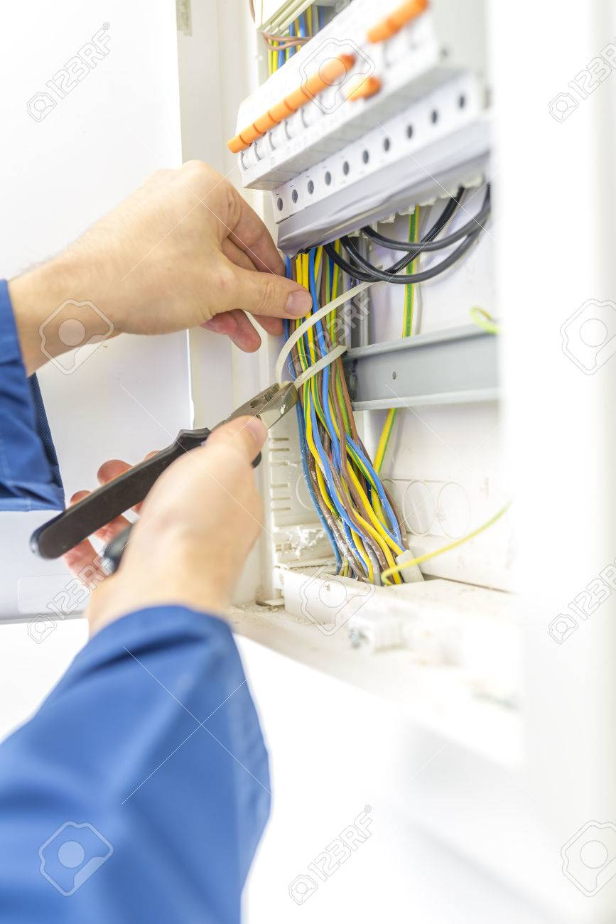 electrician checking the wiring in a fuse box providing the electrician checking the wiring in a fuse box providing the electrical supply to a domestic residence