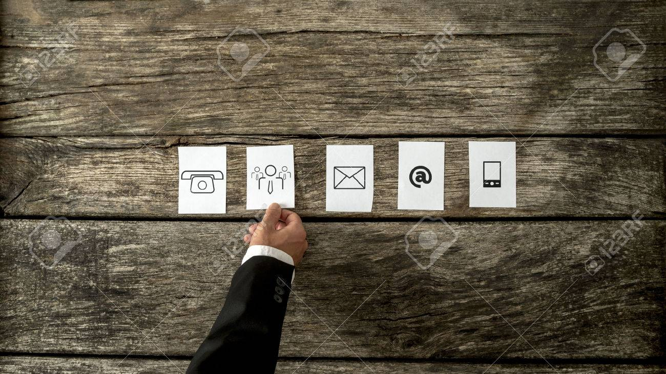 High angle view of businessman laying out white cards with communication and people icons on a rustic wooden background. Stock Photo - 44155182