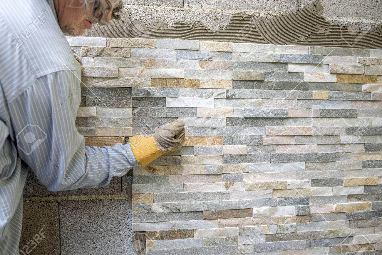 Uomo più anziano decorare una parete con piastrelle ornamentali