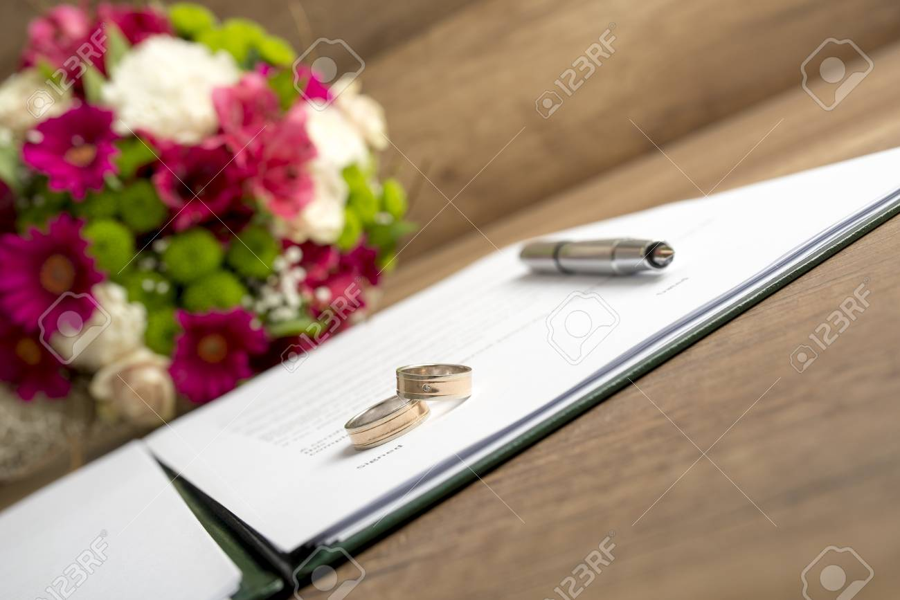 wedding register with pen bride and groom rings and bouquet stock