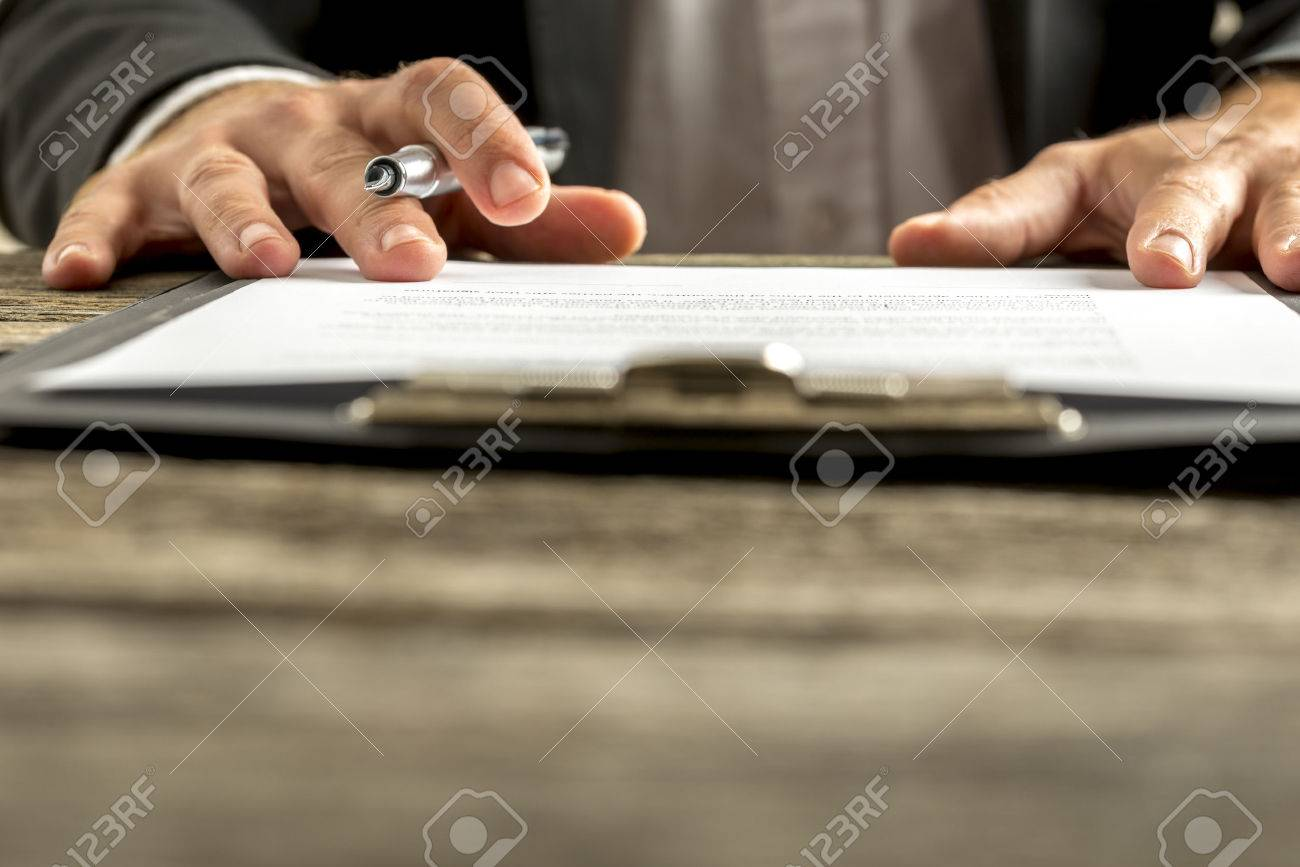 Closeup of male hand about to sign a subscription or application papers clipped on blue folder on wooden desk. - 44284781