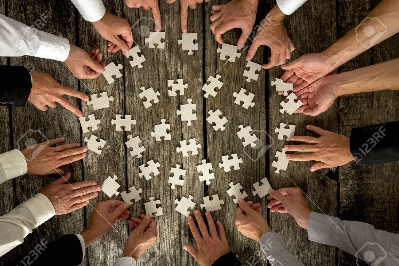 Teamwork Concept - High Angle View of Businessmen Hands Forming Circle and Holding Puzzle Pieces on Top of a Rustic Wooden Table. Stock Photo - 44906031