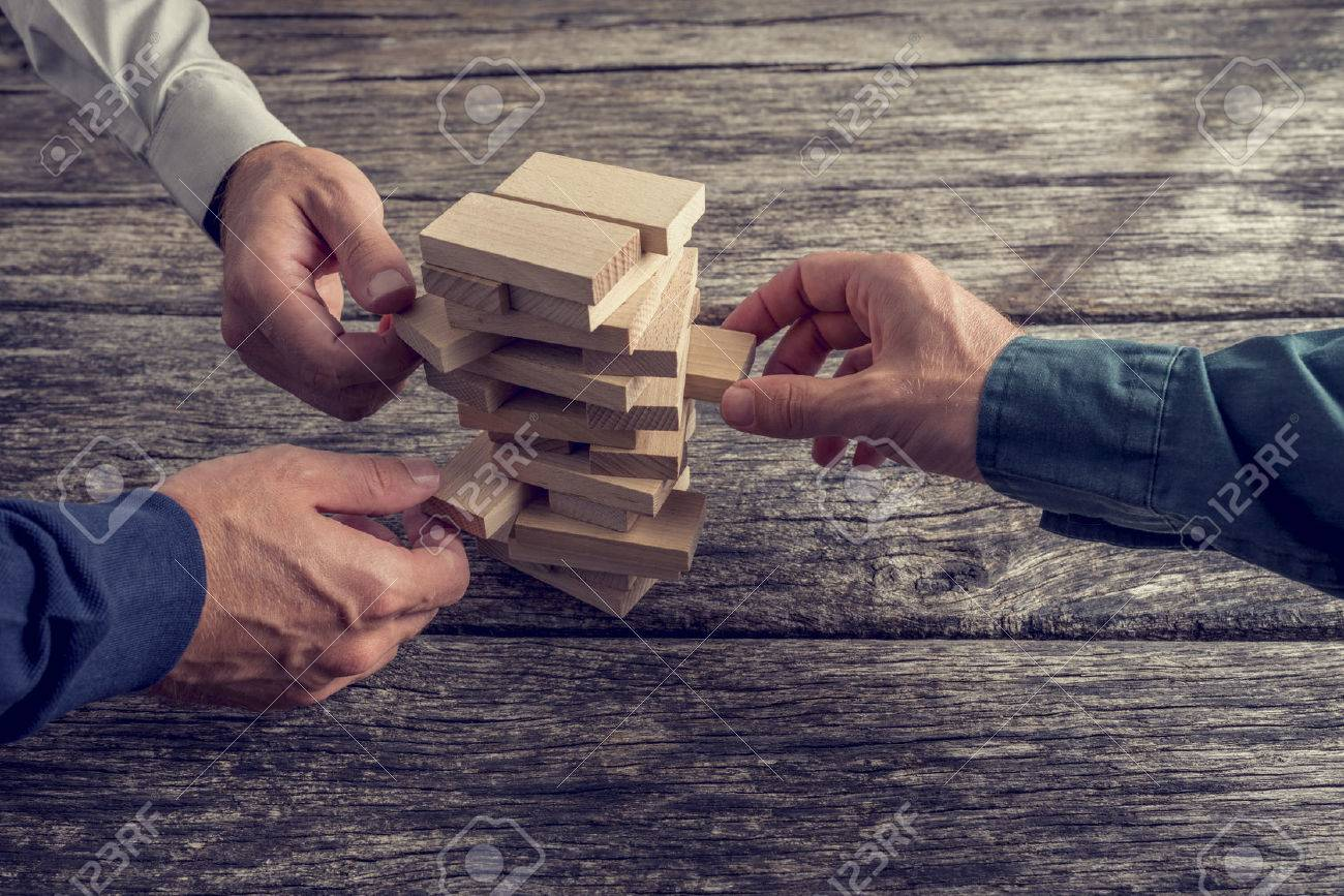 Three Businessmen Hands Playing Wooden Tower Game on Top of a Rustic Wooden Table. Conceptual of Teamwork, Strategy and Vision. Stock Photo - 44906033